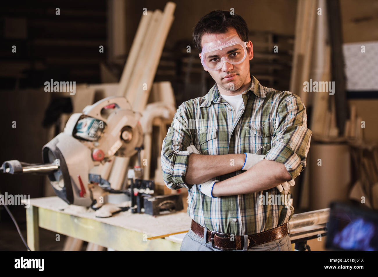 Handsome carpenter in protective glasses is looking at camera and smiling while standing near his wooden object Stock Photo