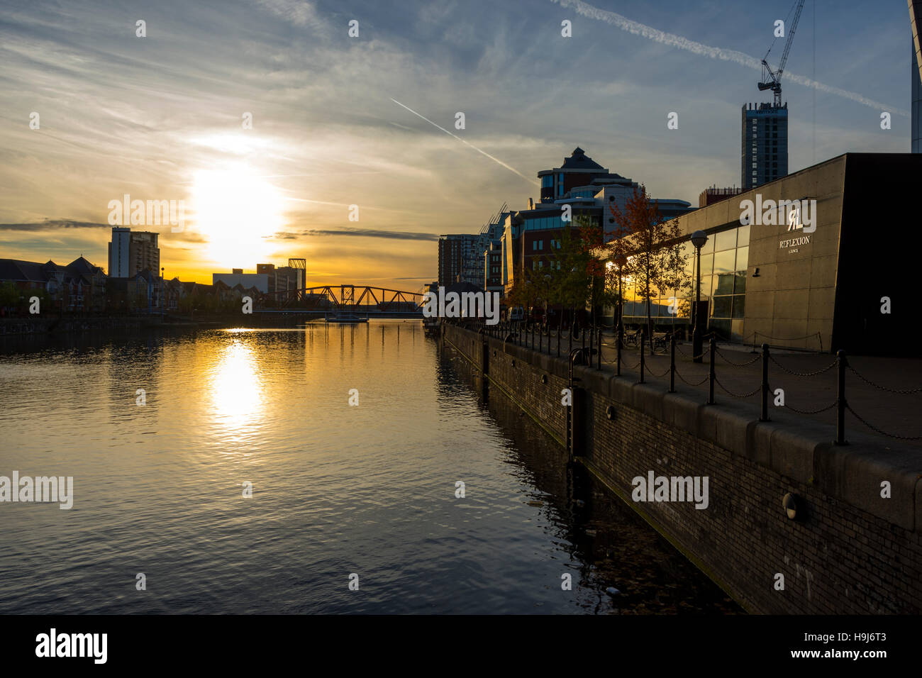 Sunset over Erie Basin, Salford Quays, Manchester, England, UK. On the right is the 'Reflexion' lounge bar. - Stock Image
