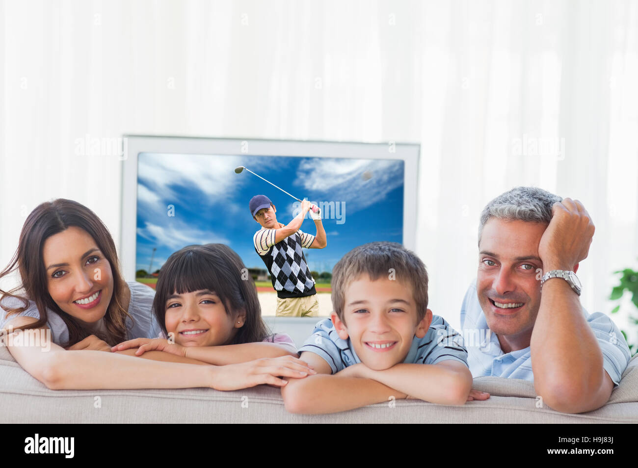 Composite image of family in sitting room smiling at camera - Stock Image