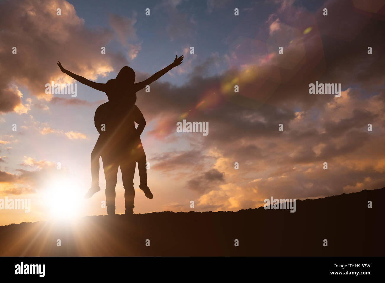 Composite image of happy casual man giving pretty girlfriend piggy back Stock Photo