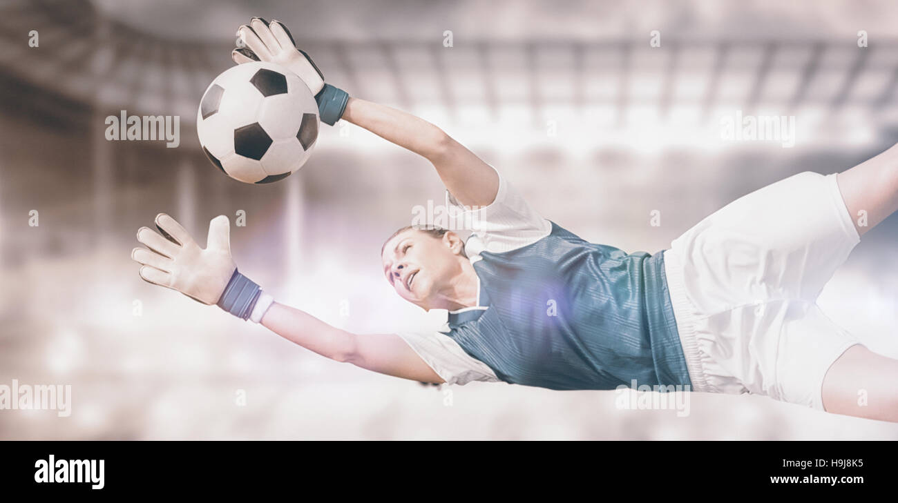 Composite image of woman goalkeeper stopping a goal - Stock Image