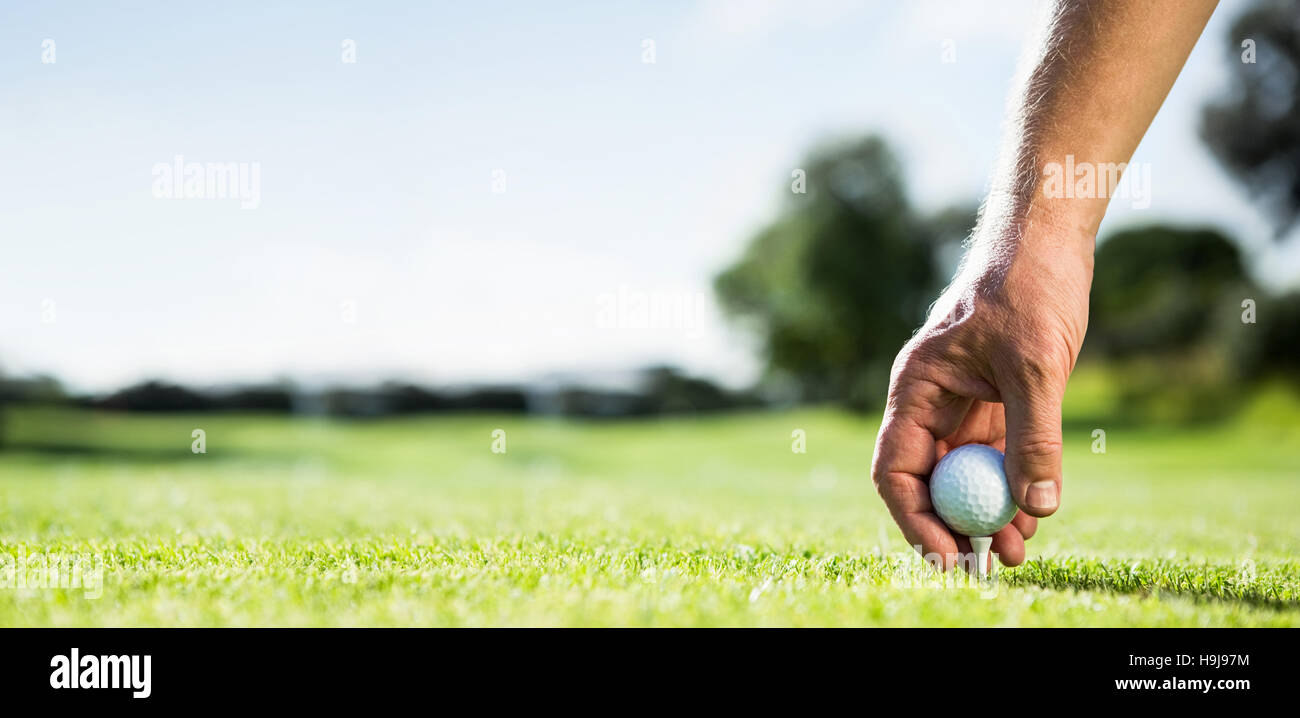 Golfer placing golf ball on tee - Stock Image
