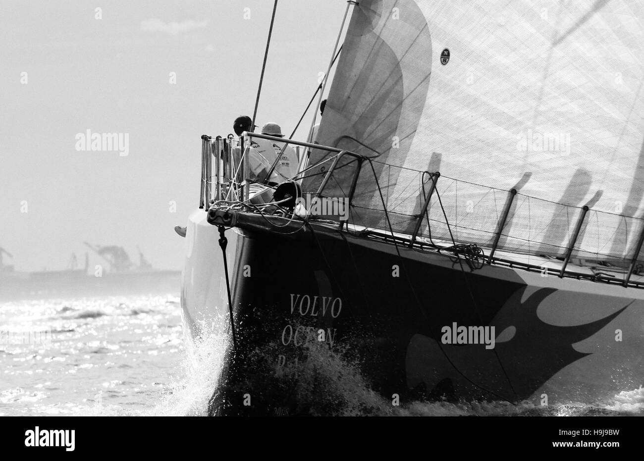 Bow of Volvo Ocean Race 70 foot sailing yacht slashing the water - Stock Image