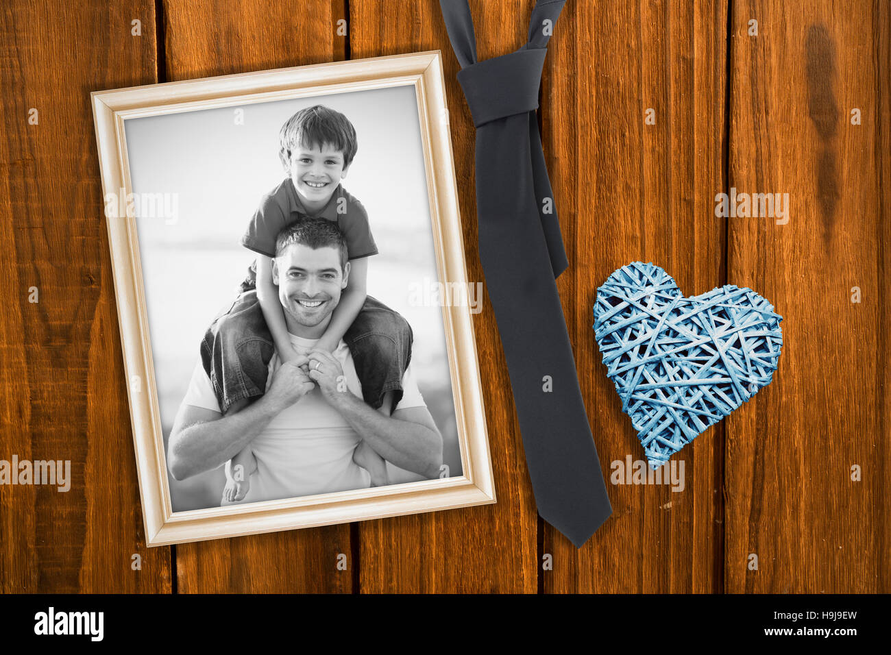 Composite image of father giving son piggyback ride - Stock Image