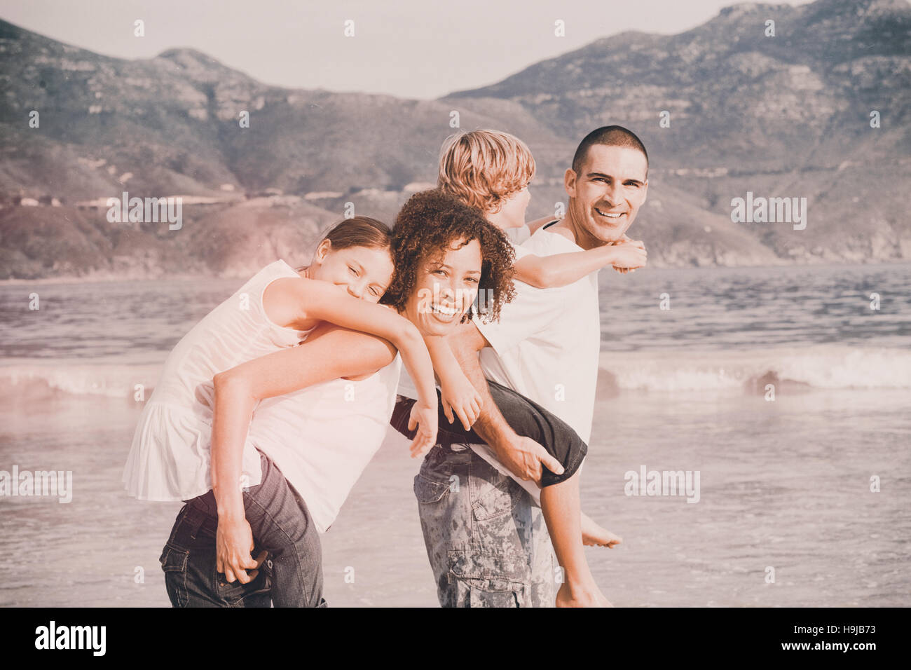Happy family playing on the beach - Stock Image