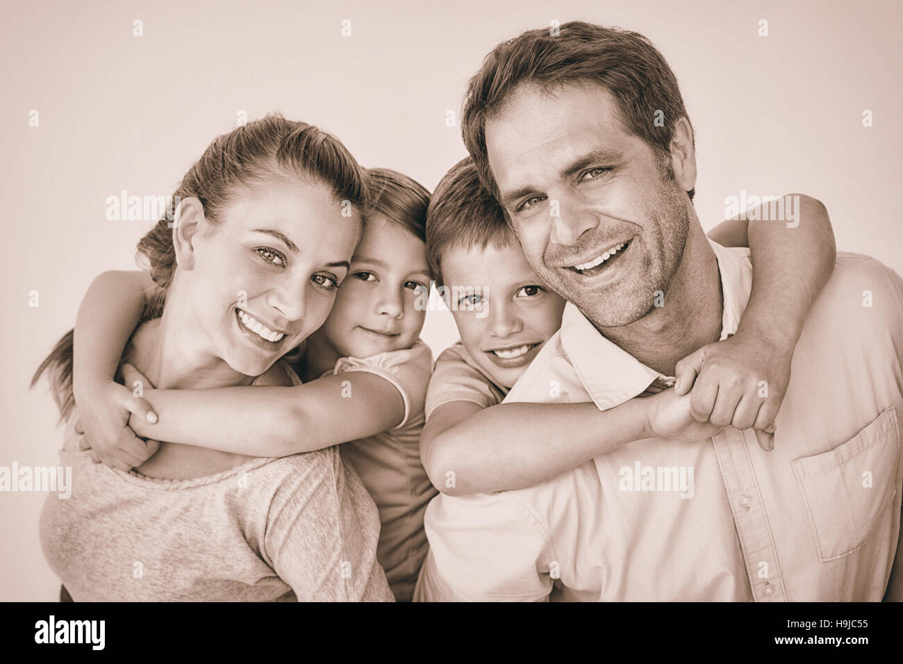 Smiling young family looking at camera together - Stock Image