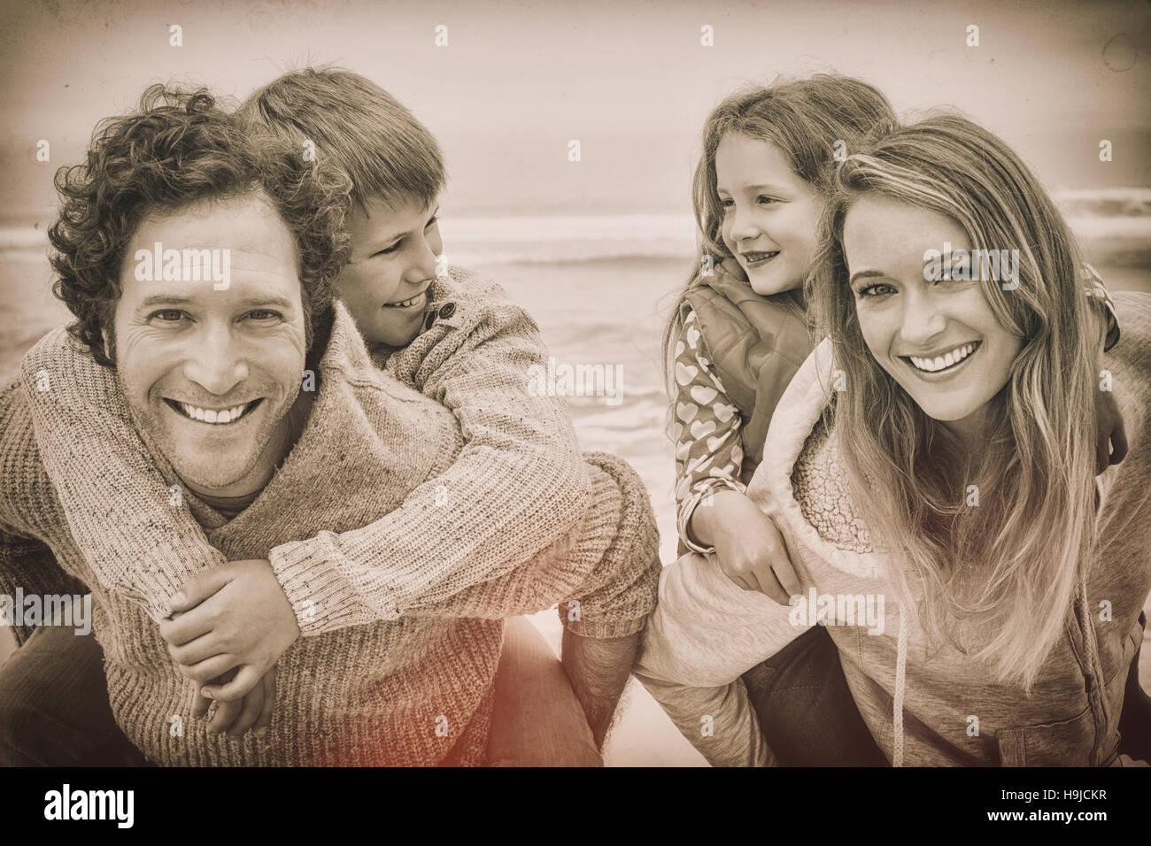 Happy couple piggybacking kids at beach - Stock Image