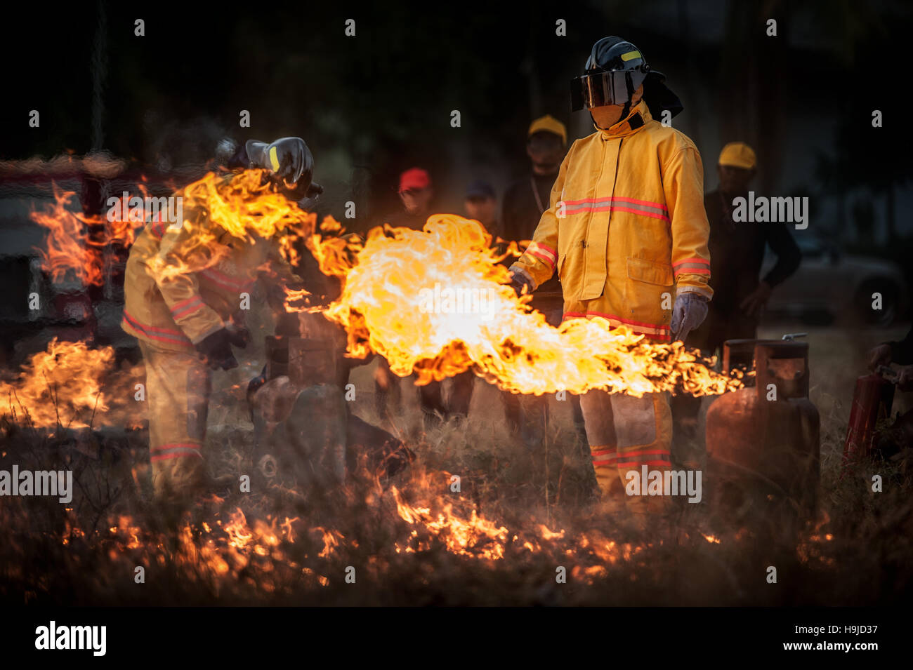 Silhouette of Firemen fighting a raging fire with huge flames of burning timber - Stock Image