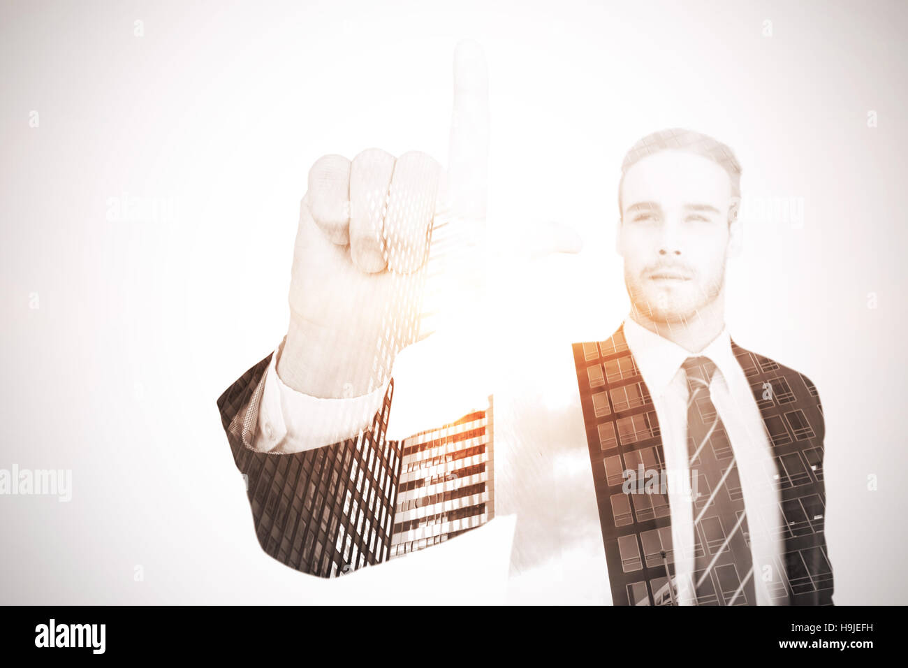 Unsmiling businessman in suit pointing up his finger - Stock Image
