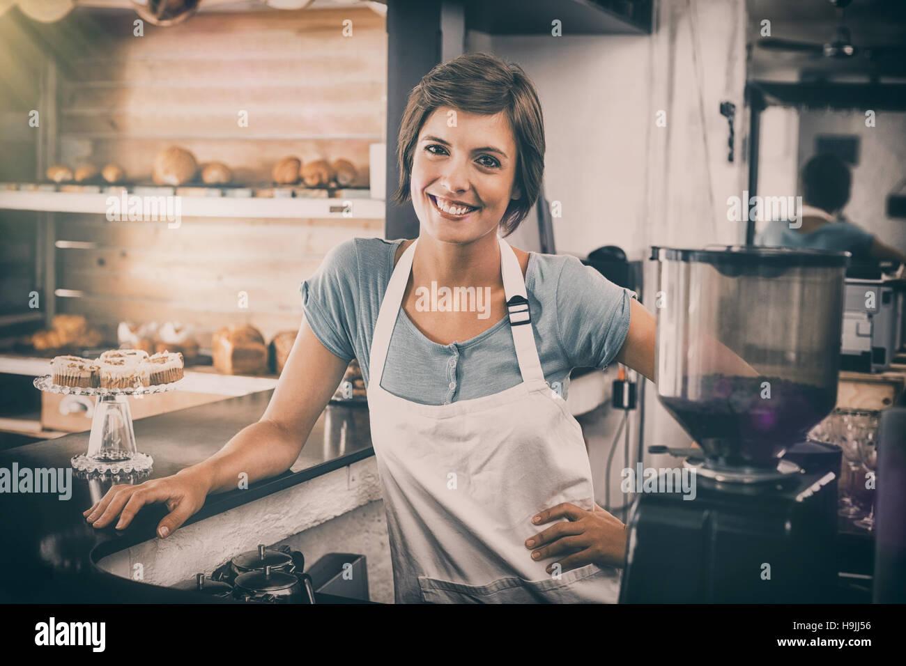 Pretty barista smiling at camera - Stock Image
