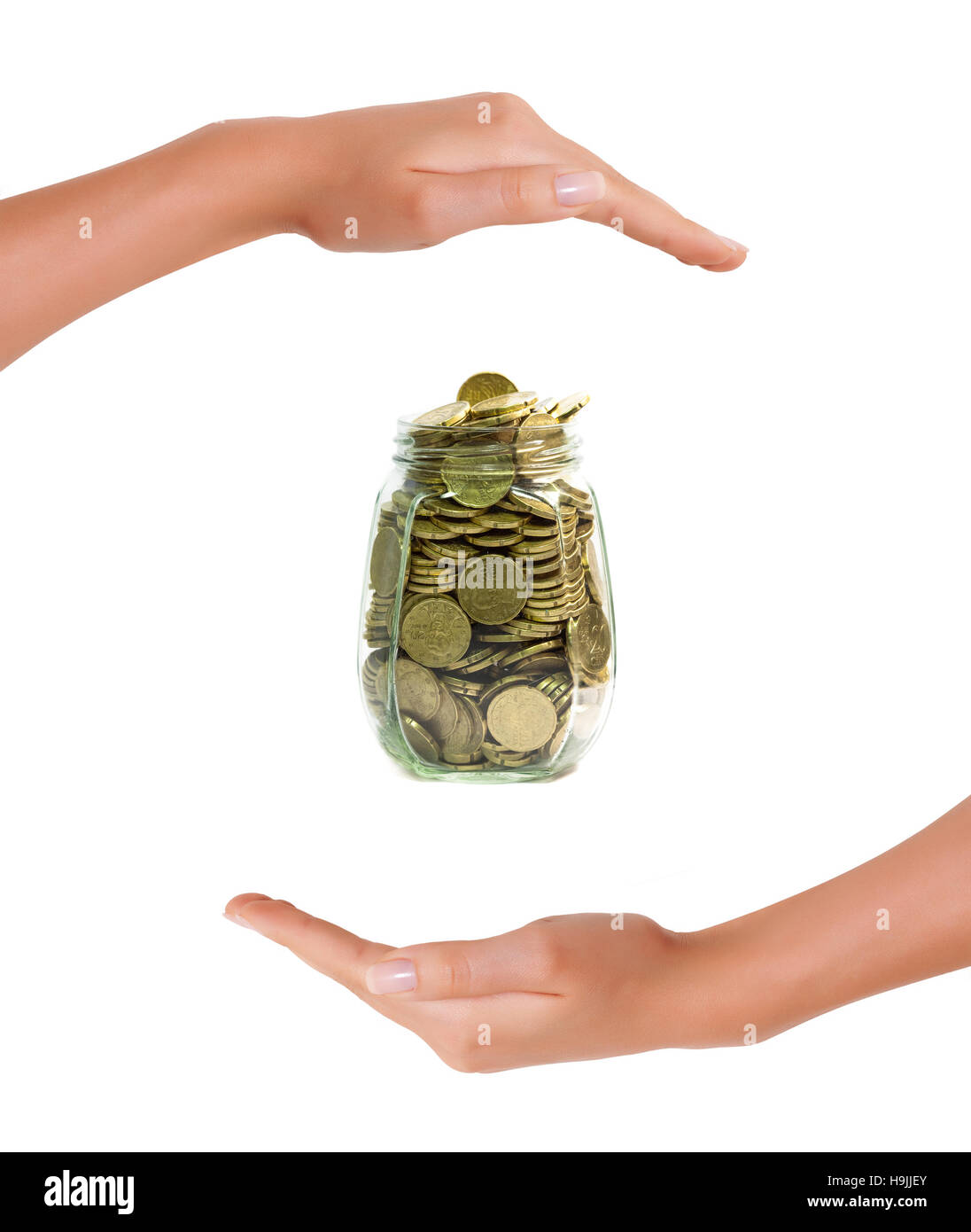 Euro coins in a jar  between hands on white background, concept of saving money and protection of investment - Stock Image