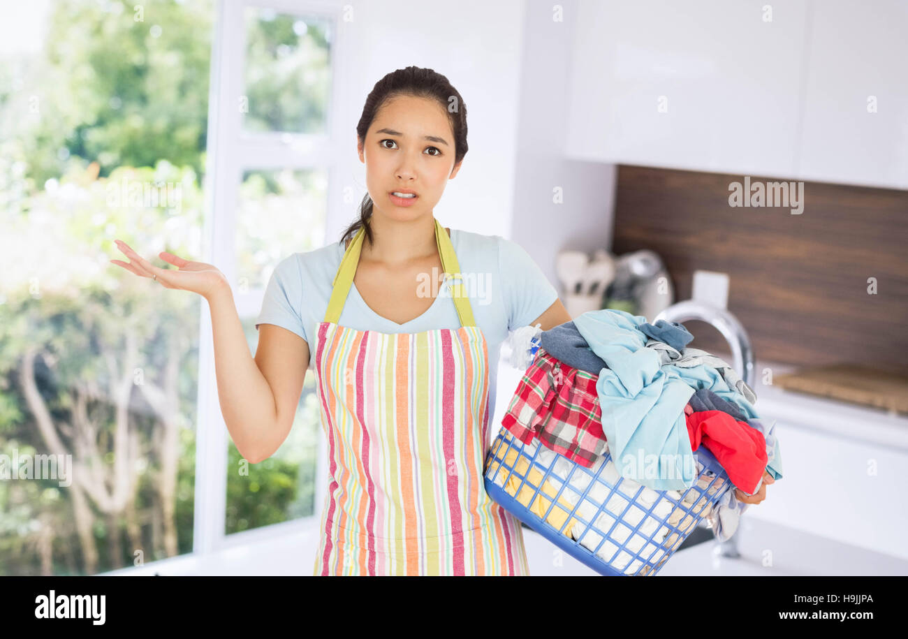 Composite image of puzzled young woman holding laundry basket full of dirty laundry - Stock Image
