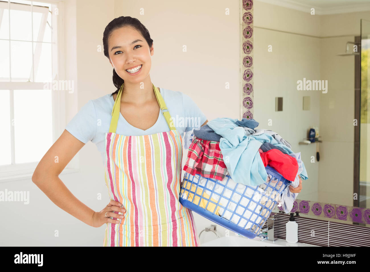 Composite image of happy woman with laundry basket - Stock Image