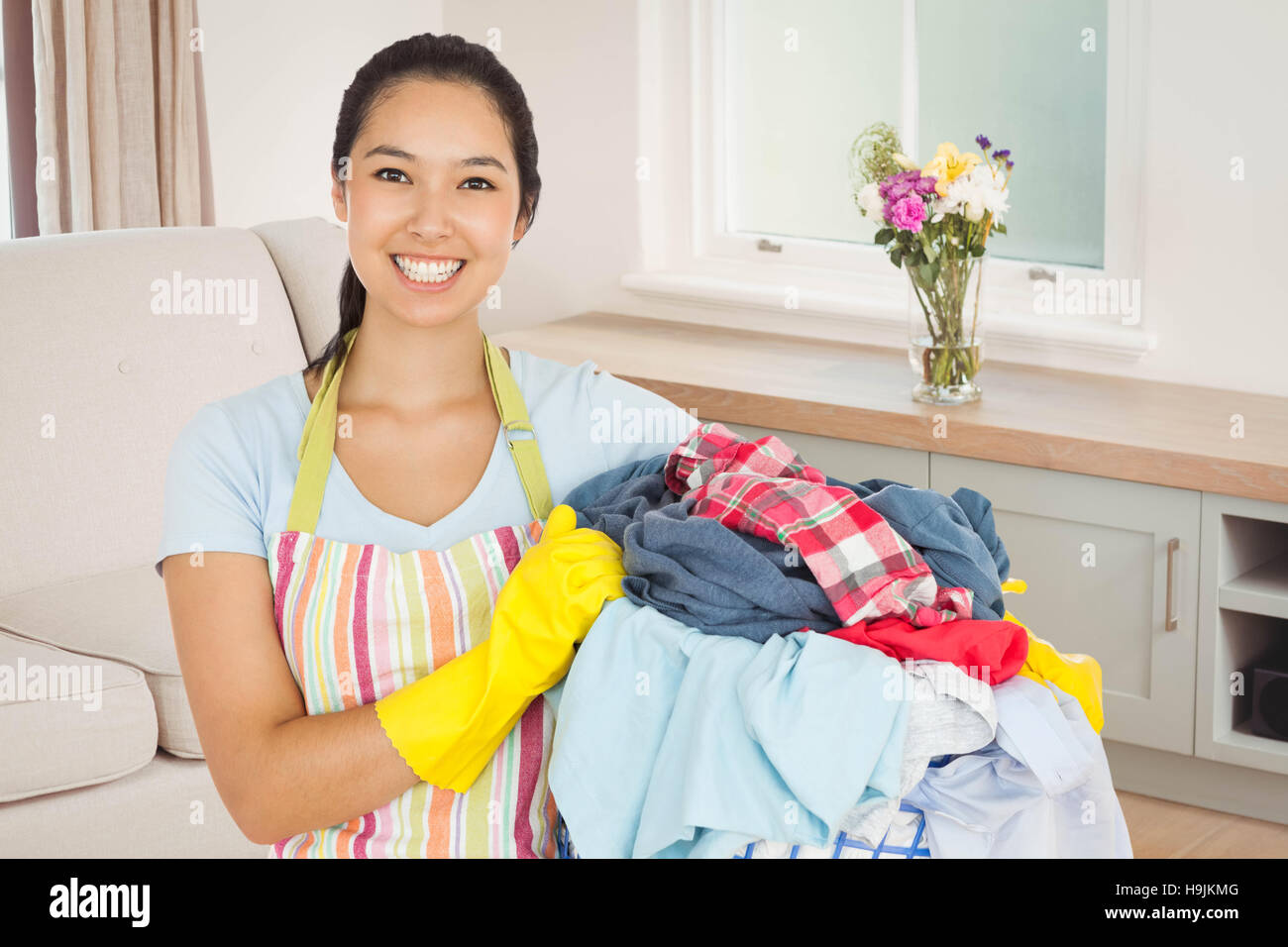 Composite image of laughing woman holding laundry basket - Stock Image