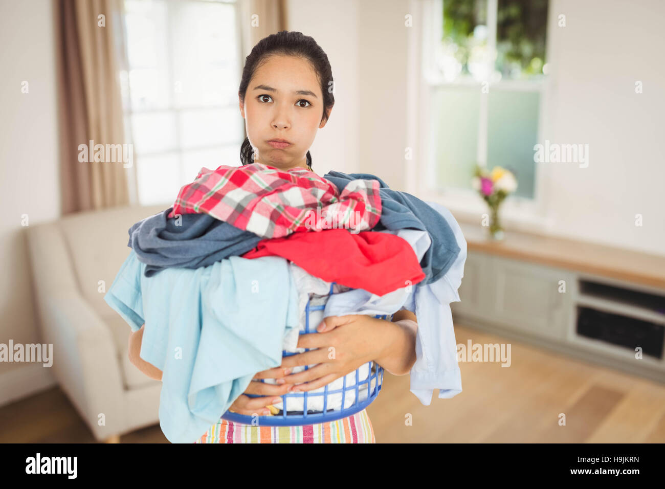 Composite image of tired woman holding full laundry basket - Stock Image