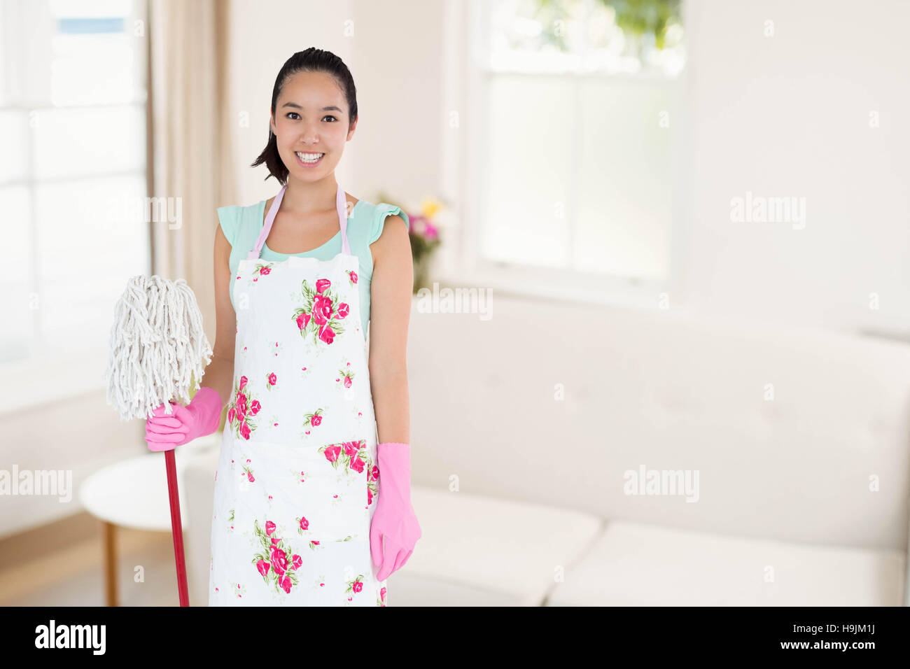 Composite image of happy woman with mop and bucket - Stock Image