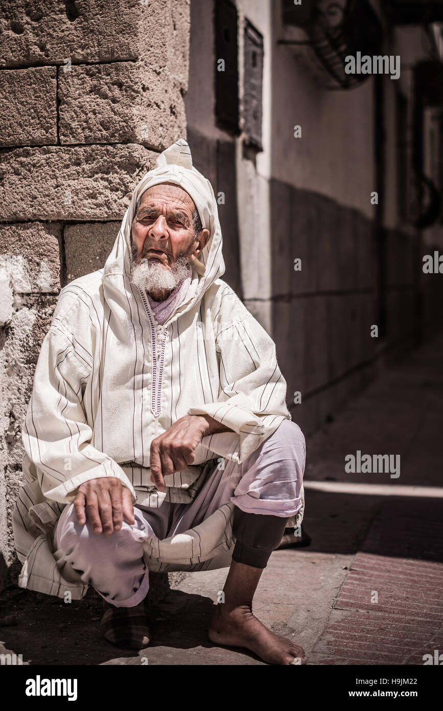 A portrait photograph of an elderly traditional Moroccan man in tradition clothes seated in a street in Morocco, Stock Photo