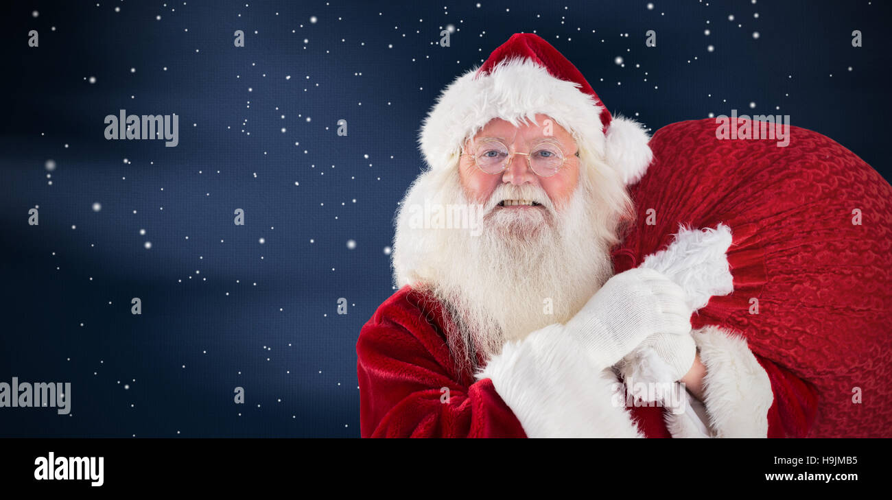 Composite image of jolly santa carries his sack - Stock Image