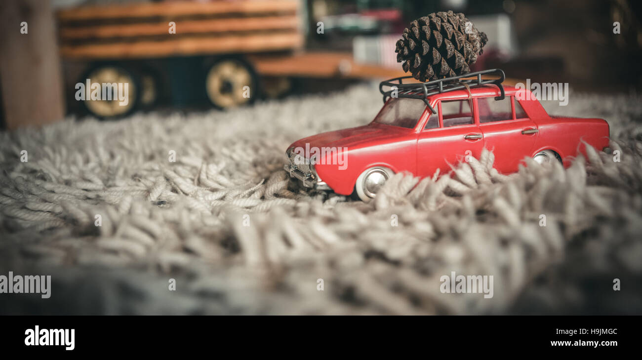 Toy car carrying christmas pine cone Stock Photo
