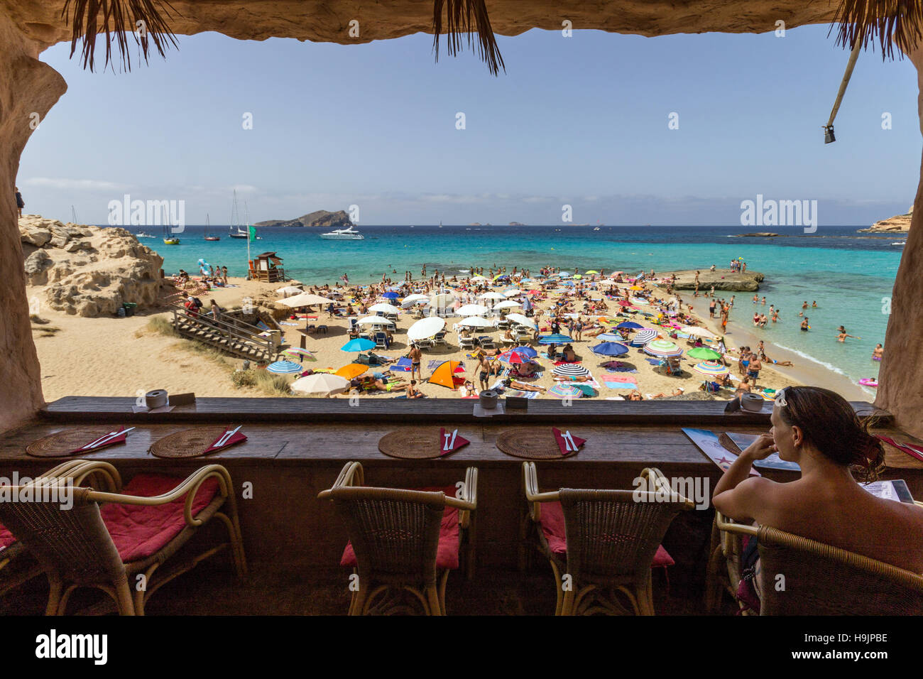 Spain, Balearic Island, Ibiza, Cala Comte beach, woman sitting at the cafe - Stock Image