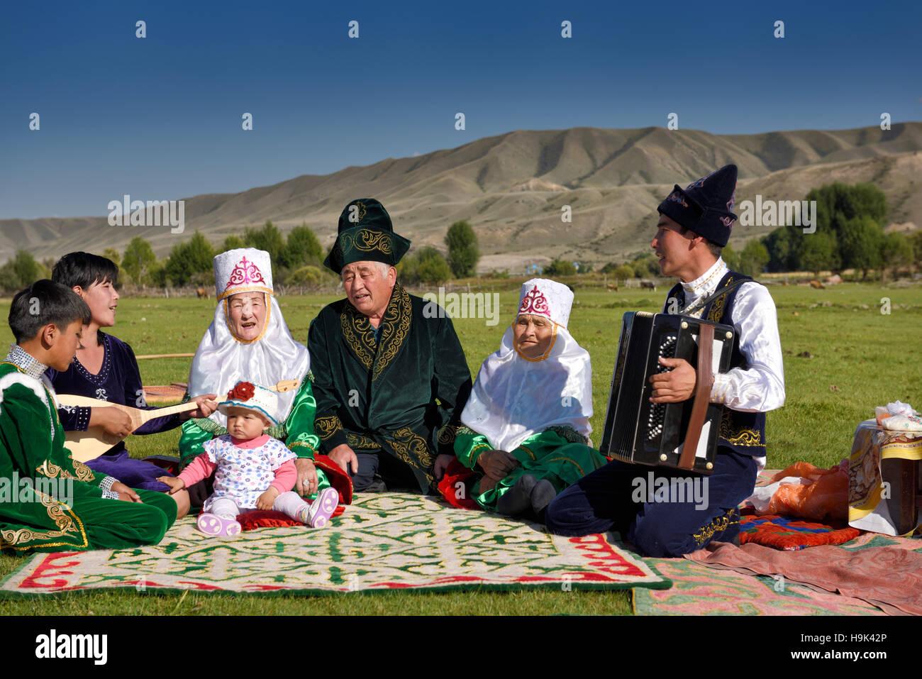 Traditional Kazakh family singing at a picnic in pastureland of Saty Kazakhstan - Stock Image