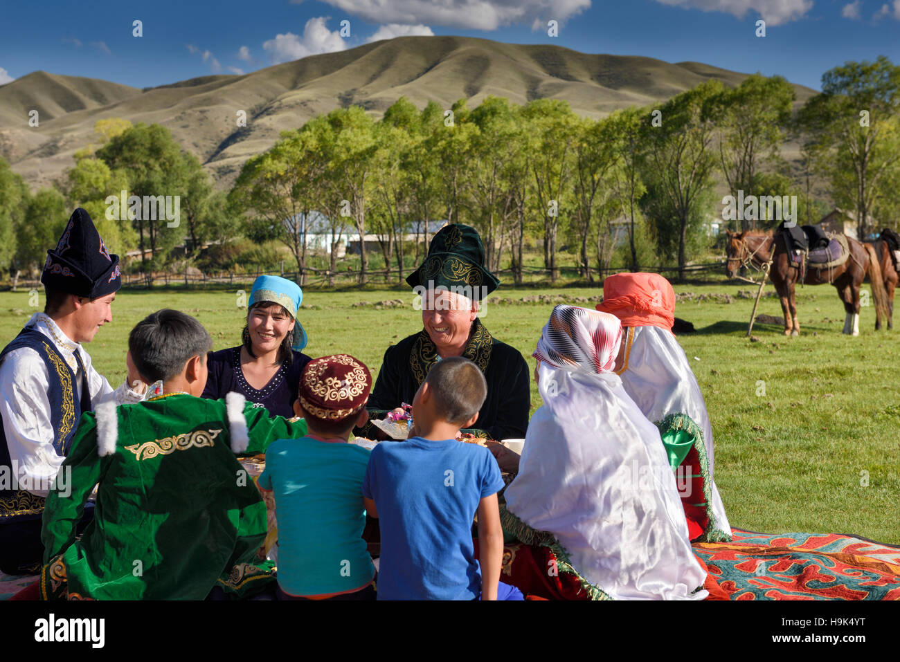 Laughing family in traditional garb at a picnic in pasture of Chilik river valley at Saty Kazakhstan - Stock Image