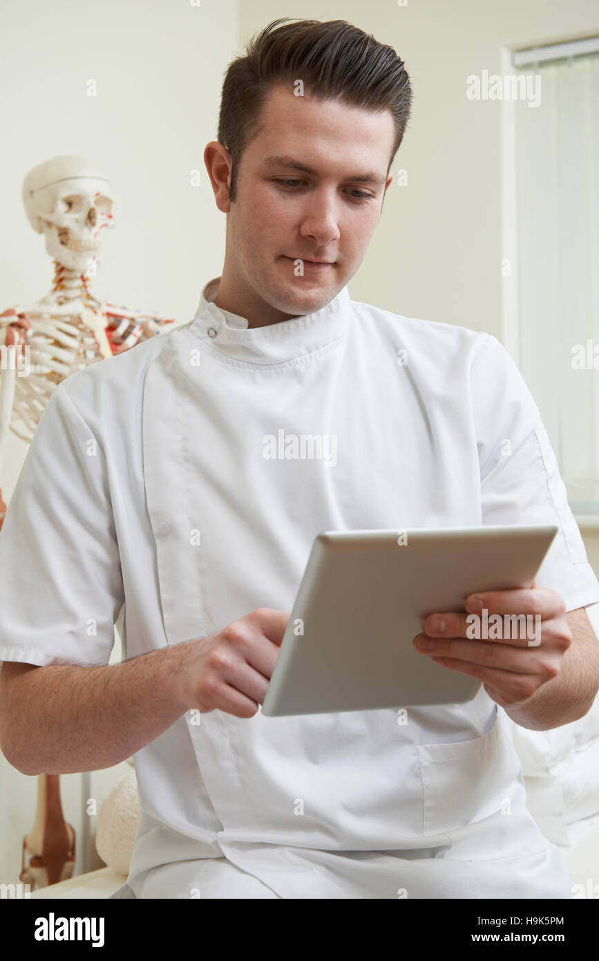 Male Osteopath In Consulting Room Using Digital Tablet - Stock Image
