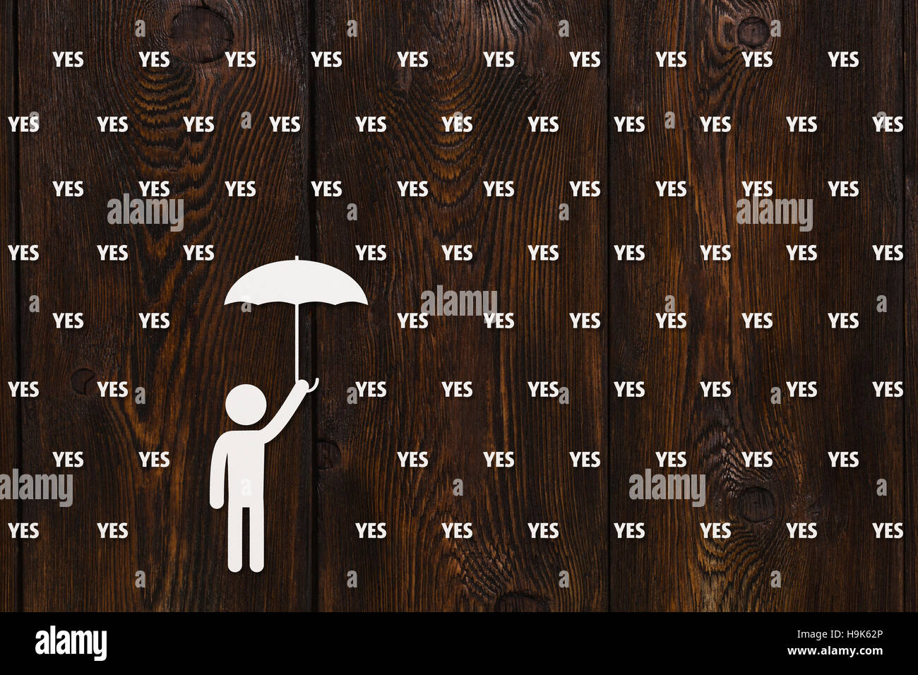 Man with umbrella standing in rain of words, abstract concept - Stock Image