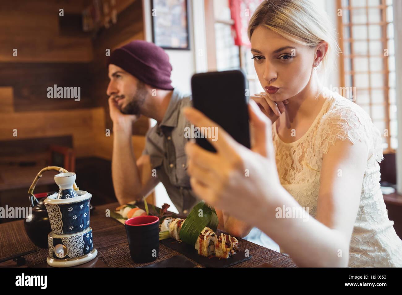 Woman taking selfie while man talking on phone Stock Photo