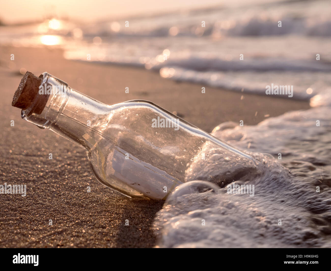 Message in the bottle washed ashore against the Sun setting down - Stock Image