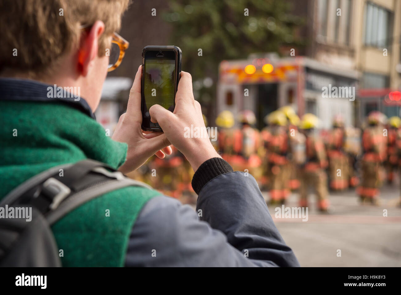 Montreal, CA - 23 Nov 2016: Male Pedestrian takes pictures with smartphone as firefighters work on 'Cafe Amusement - Stock Image