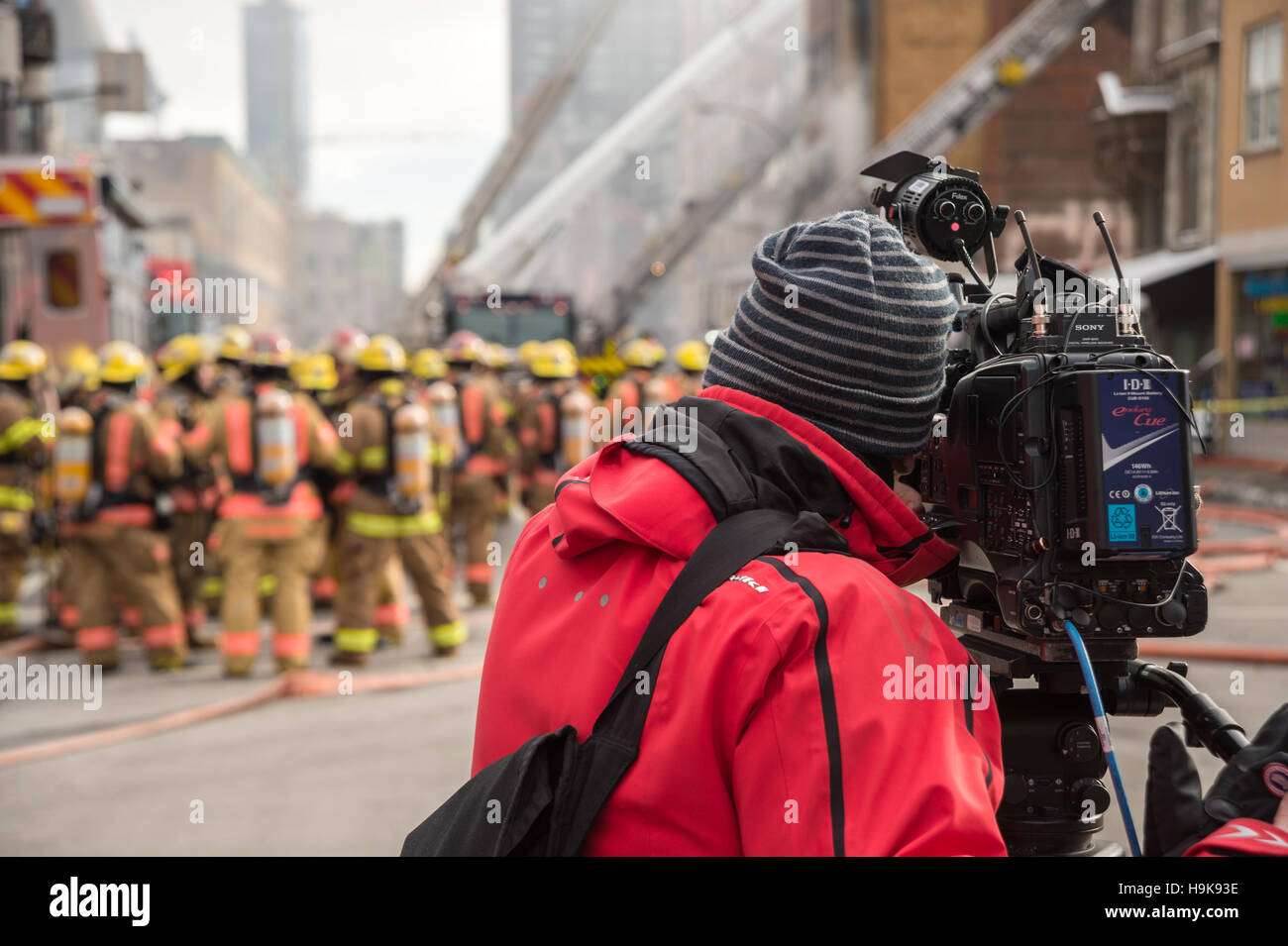Montreal, CA - 23 Nov 2016: A cameraman is filming firefighters working on 'Cafe Amusement 68' building - Stock Image