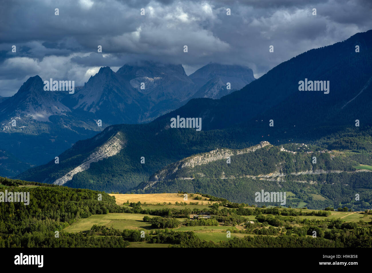 Paragliding above the village of Saint Vincent Les Forts with view on the Seolane Des Besses and Ailette mountains. - Stock Image