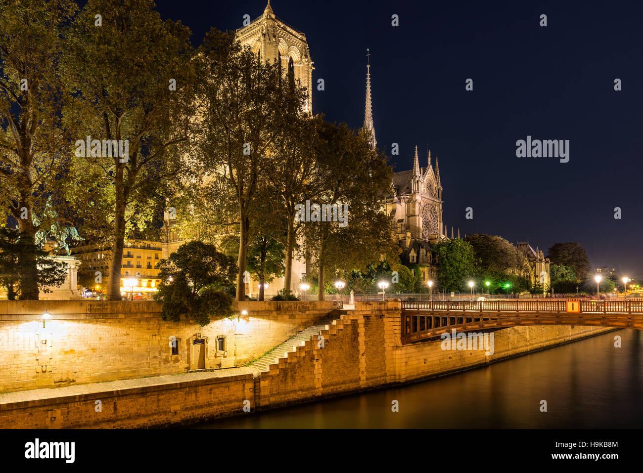 Notre Dame de Paris cathedral illuminated at twilight with the Seine River and the Pont au Double. Ile de La Cite. - Stock Image