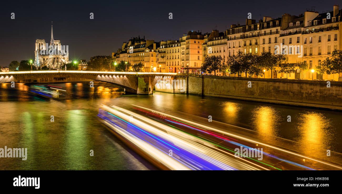 Notre Dame de Paris cathedral illuminated with the Seine River and the Tournelle Bridge. Ile Saint Louis, Paris, - Stock Image