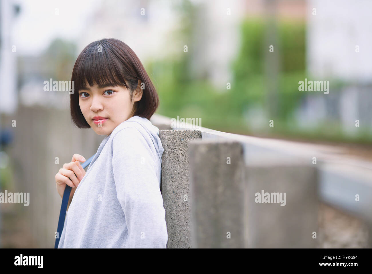 Young Japanese woman by a railway track outside Stock Photo