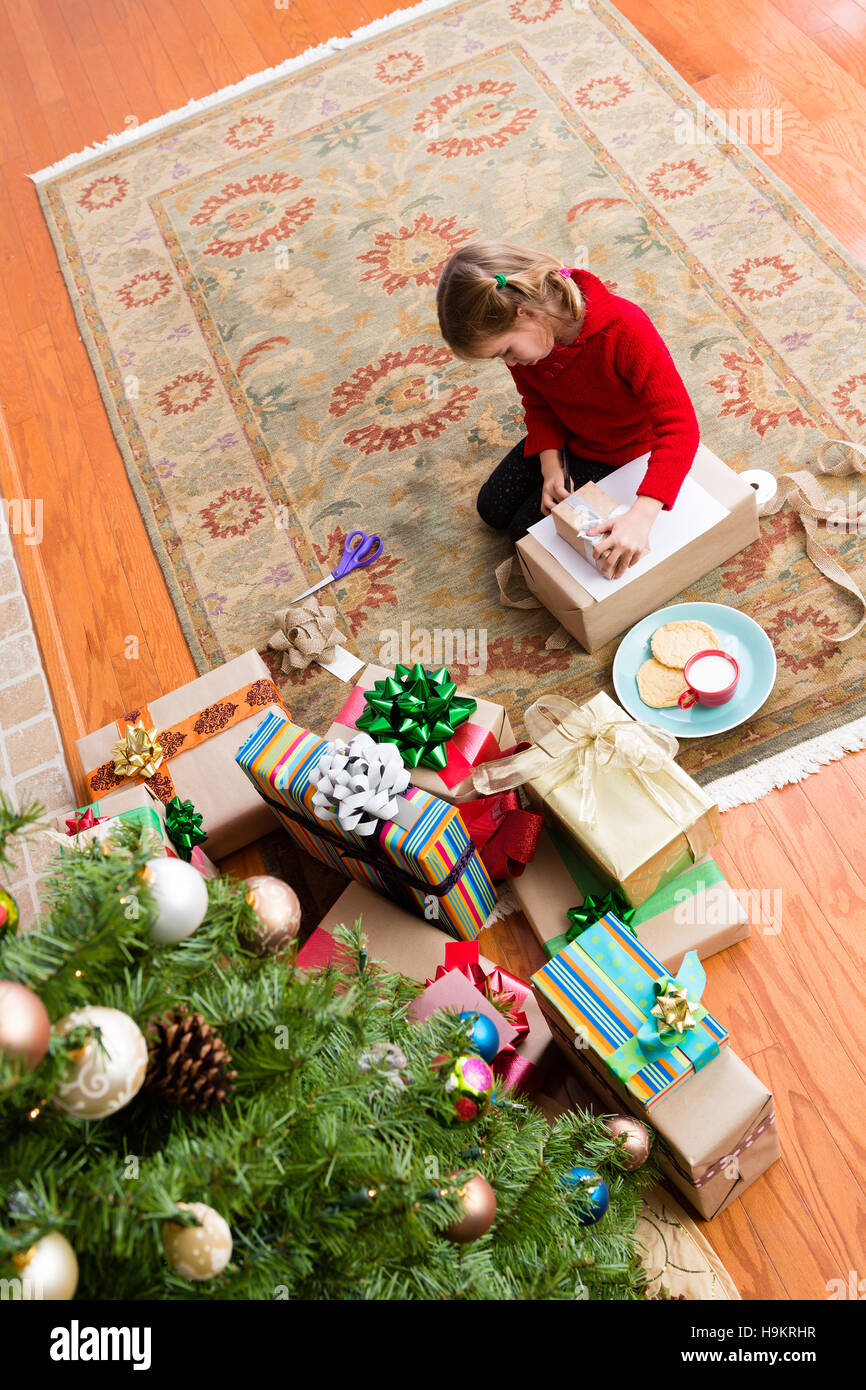 Little five year old girl wrapping a Christmas gift as she sits at ...