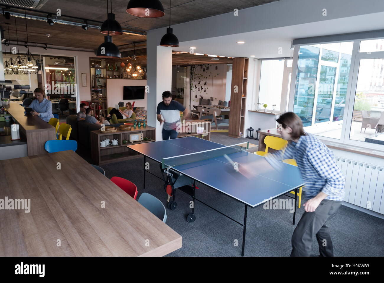 Two Young Start Up Business Man Playing Ping Pong Tennis At Modern Creative  Office Space People Group Have Meeting And Brainstorming In Background