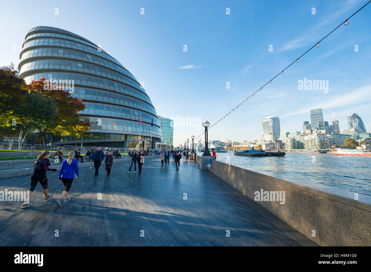LONDON - OCTOBER 28, 2016: Visitors take advantage of mild autumn afternoon on the south bank of the Thames riverside. - Stock Image