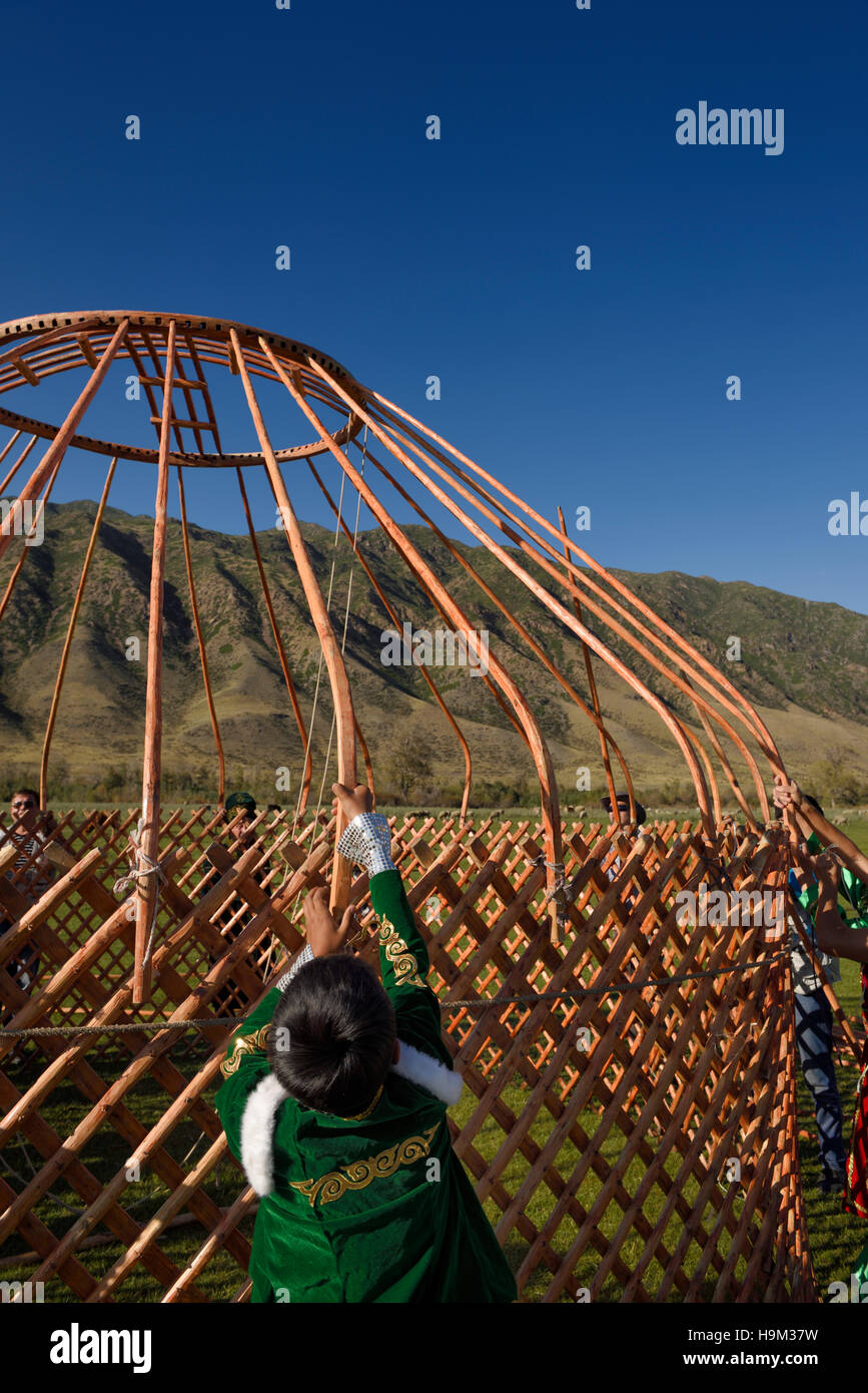 Young boy helping to assemble the wood frame of a Yurt in Saty Kazakhstan - Stock Image