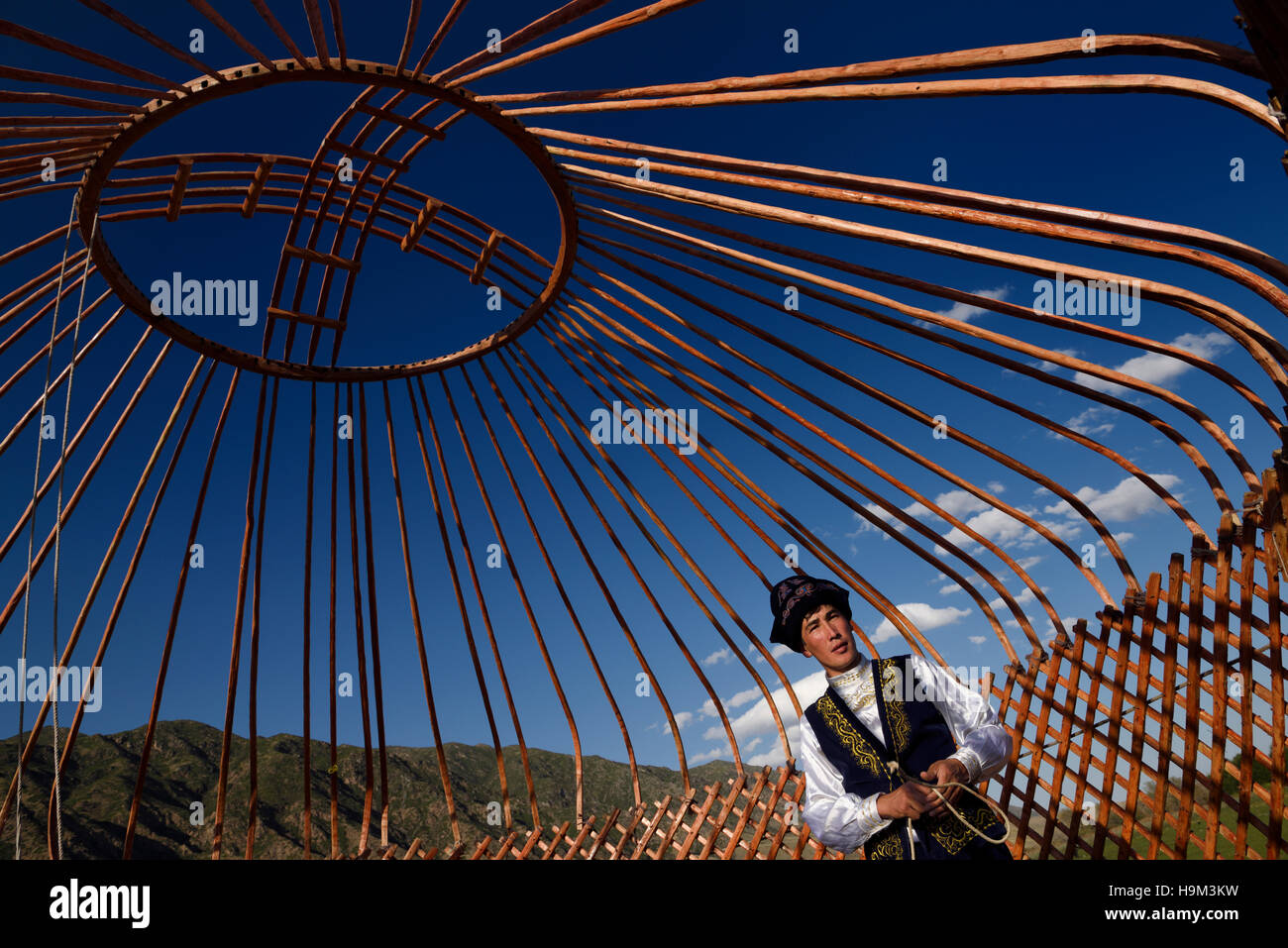 Kazakh man in traditional clothes under the wood frame of a Yurt against a blue sky Saty Kazakhstan - Stock Image
