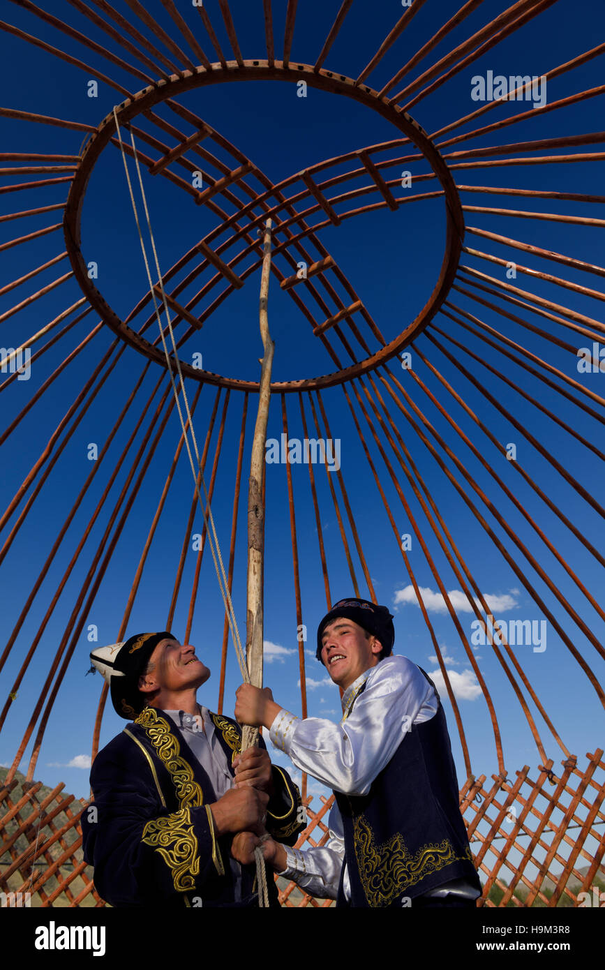 Kazakh men supporting wood frame roof of Yurt during assembly in Saty Kazakhstan - Stock Image