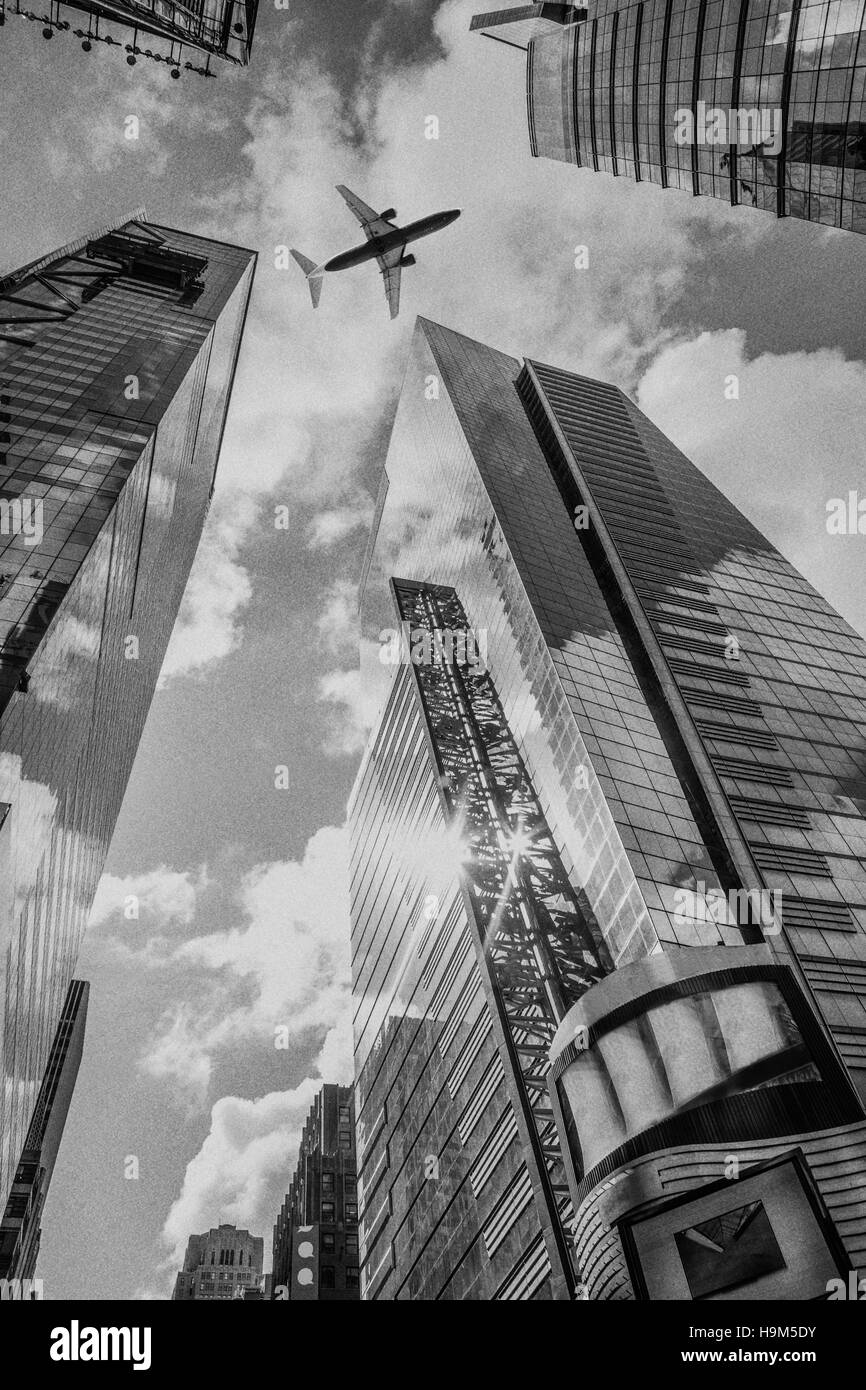 USA, New York City, skyscrapers seen from below with overflying airplane - Stock Image