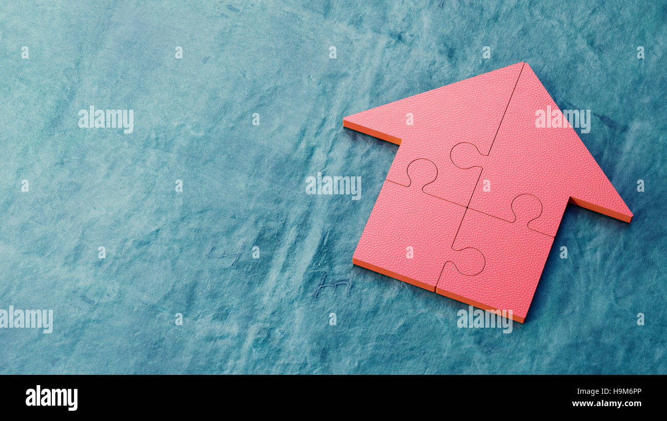 Red jigsaw house on blue background - Stock Image