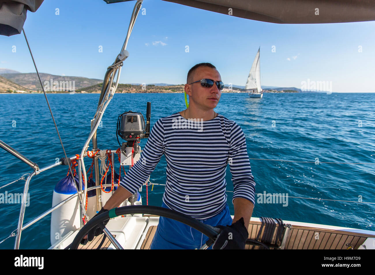 Skipper at the helm controls of a sailing yacht. Stock Photo