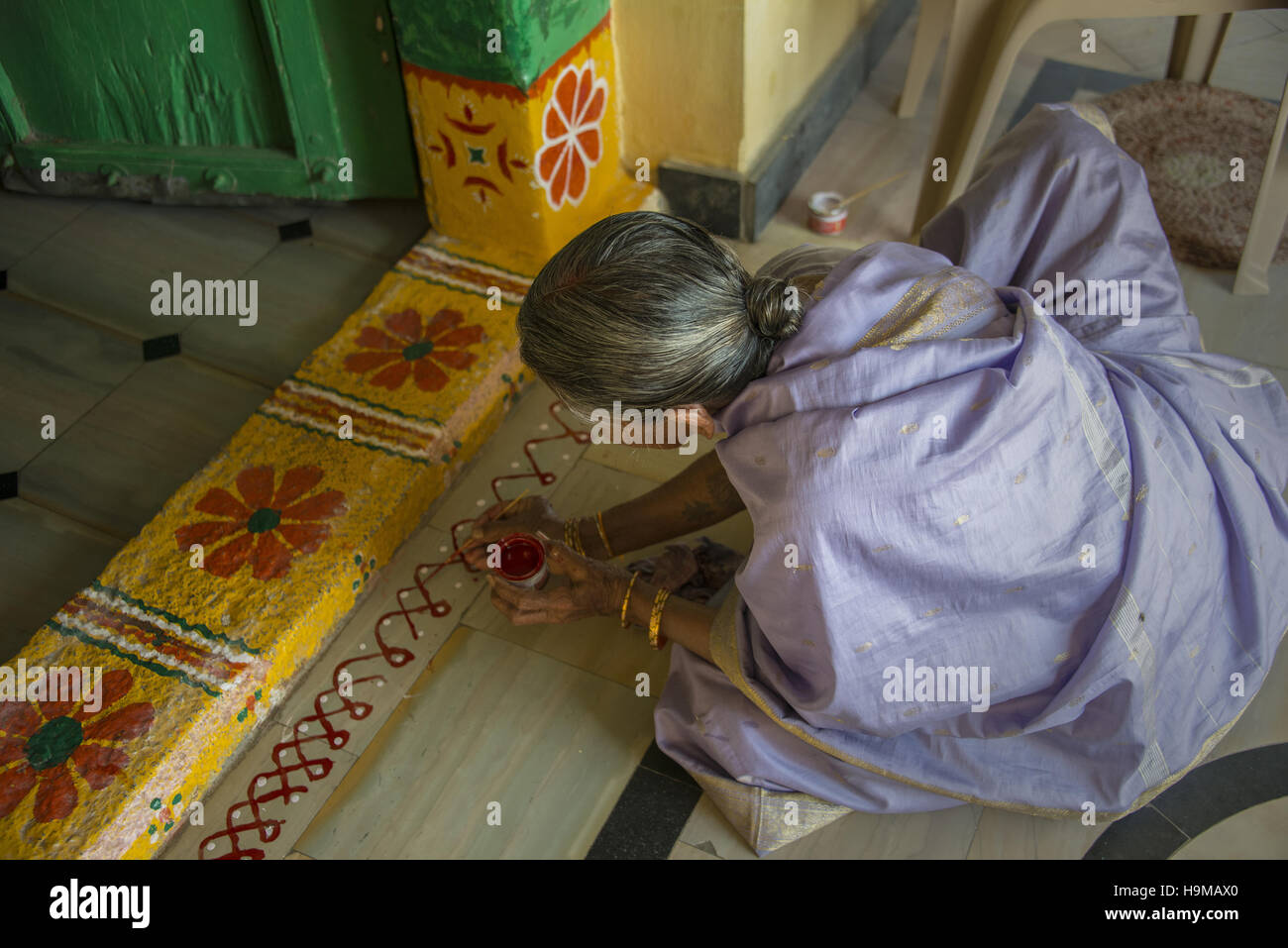 Woman painting decorative art outside the entrance of a small Hindu temple near Puttaparthi, India Stock Photo