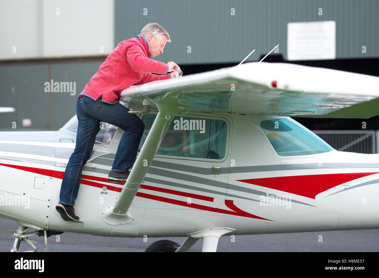 A pilot checks the wing tank fuel levels as part of the preflight checks on a Cessna 152 training aircraft at Shobdon - Stock Image