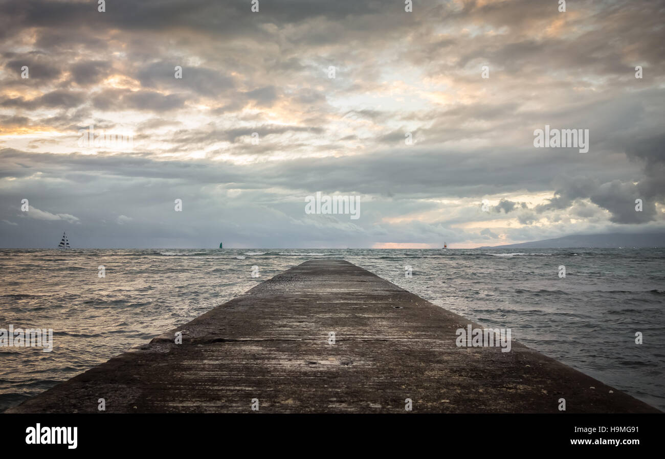 Waikiki pier stretching out toward the ocean where sail boats cruise along the cloudy evening horizon. - Stock Image
