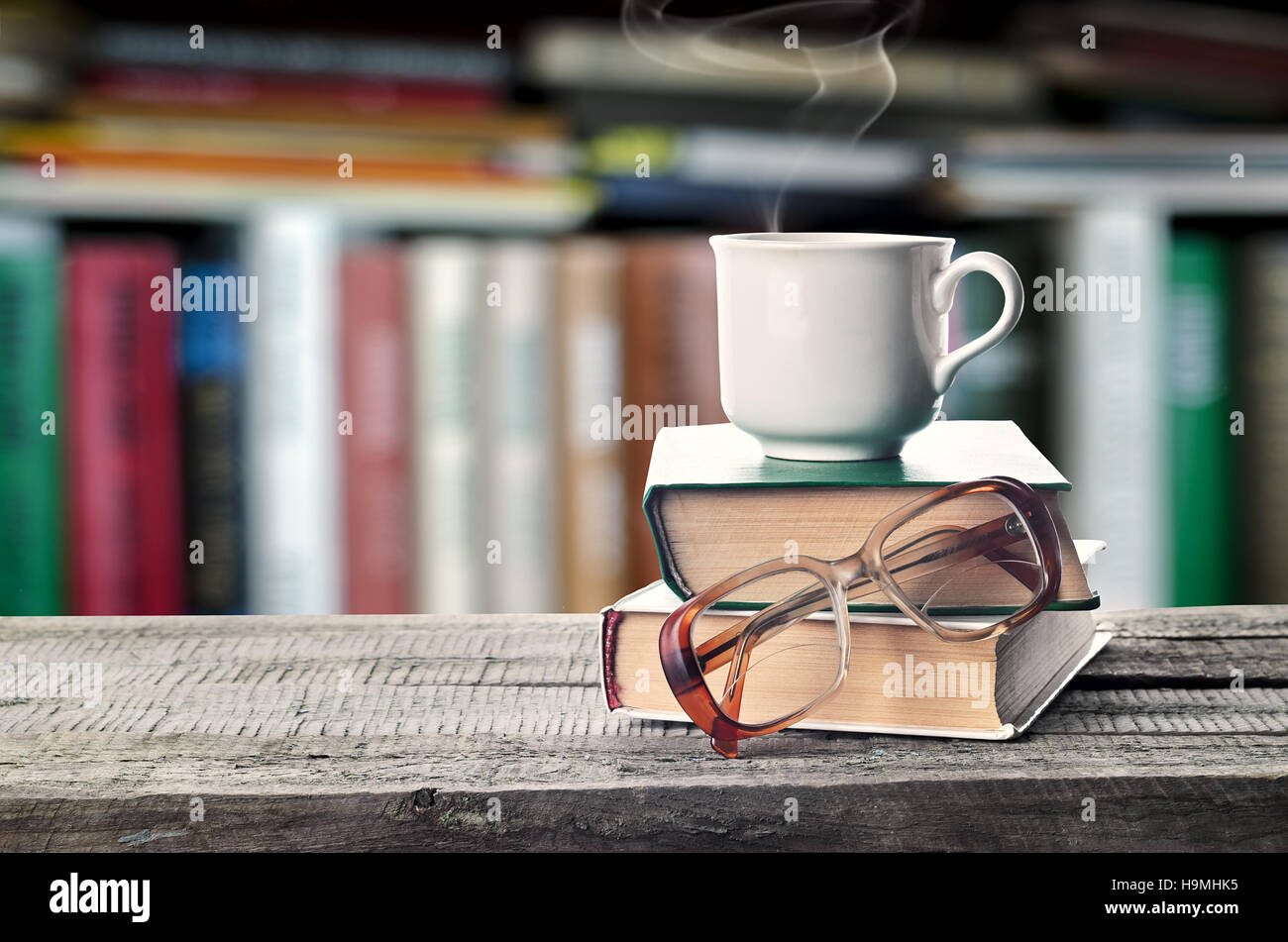 Hot Coffee Or Tea Cocoa Chocolate Cup On Book And Eyeglasses With Copy Space For Text Against The Background Of A Bookshelf Pile Books