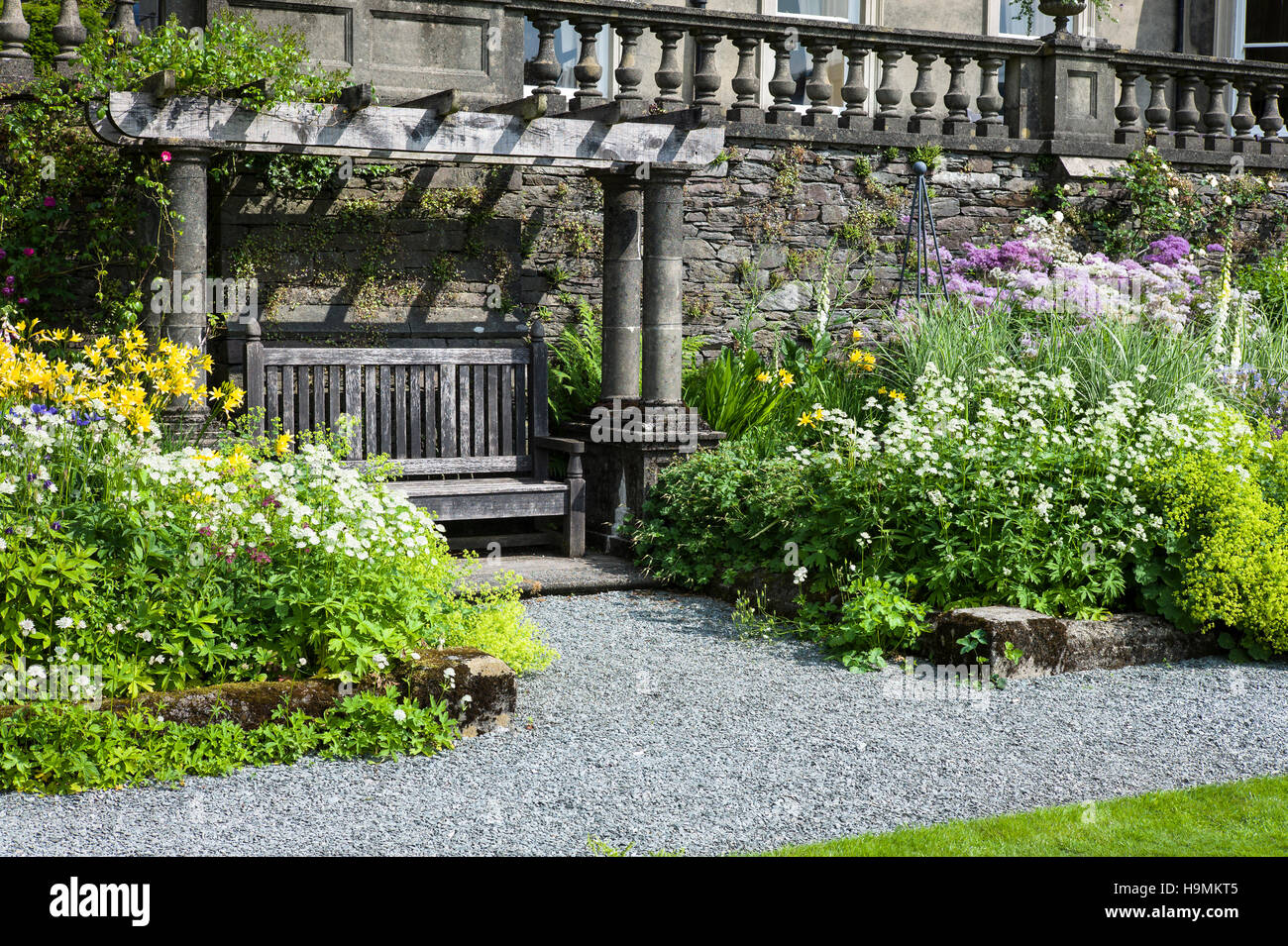 A seating arbor flanked by herbaceous flower borders at Rydal Hall Cumbria UK - Stock Image